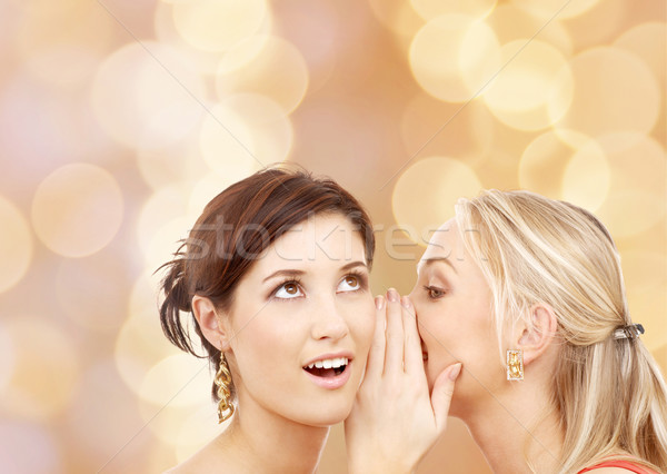 two smiling young women whispering gossip Stock photo © dolgachov