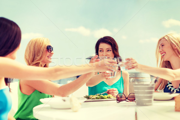 smiling girls looking at tablet pc in cafe Stock photo © dolgachov