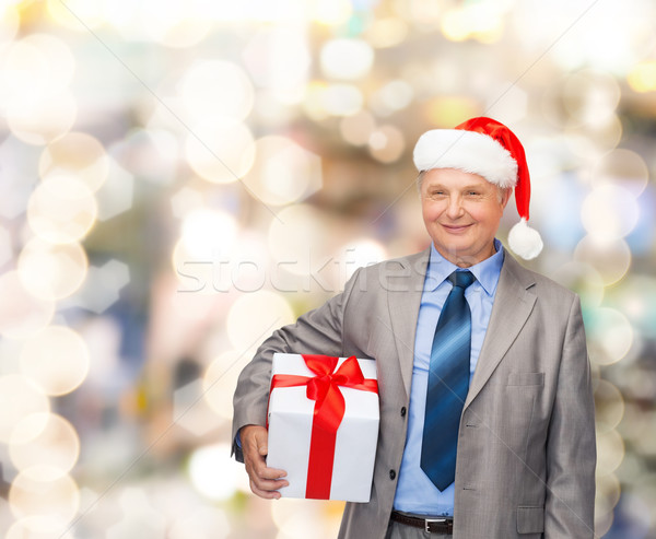 smiling man in suit and santa helper hat with gift Stock photo © dolgachov