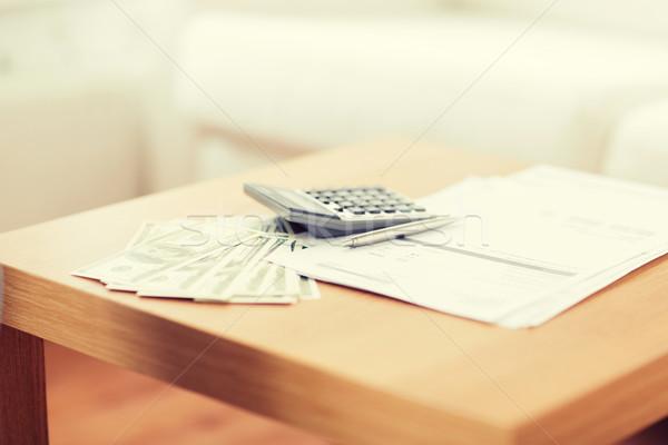 Stock photo: close up of money and calculator on table at home