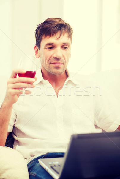 man with laptop computer and glass of rose wine Stock photo © dolgachov