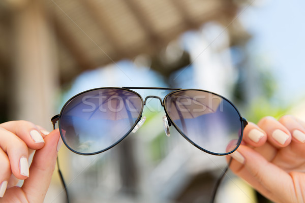 close up of hands holding shades or sunglasses Stock photo © dolgachov