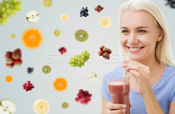 smiling woman drinking juice or shake at home Stock photo © dolgachov