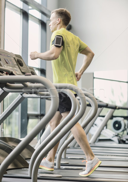 man with smartphone exercising on treadmill in gym Stock photo © dolgachov