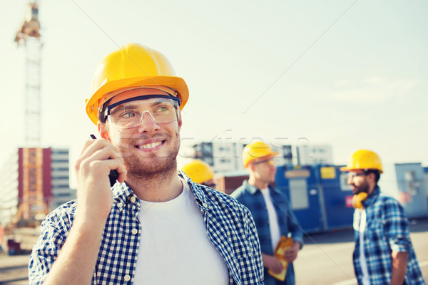 group of smiling builders in hardhats with radio Stock photo © dolgachov