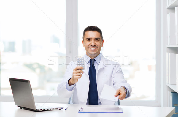 smiling doctor with tablets and laptop in office Stock photo © dolgachov