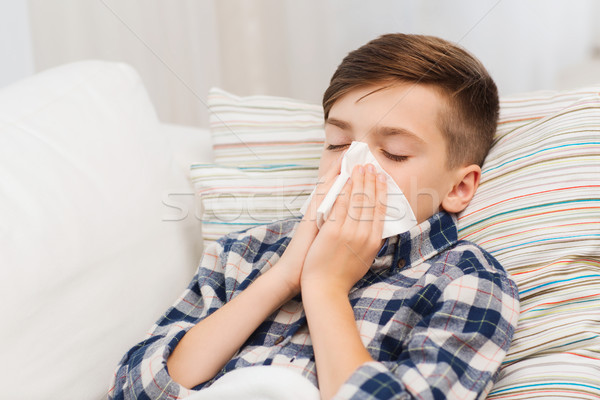 ill boy lying in bed and blowing his nose at home Stock photo © dolgachov