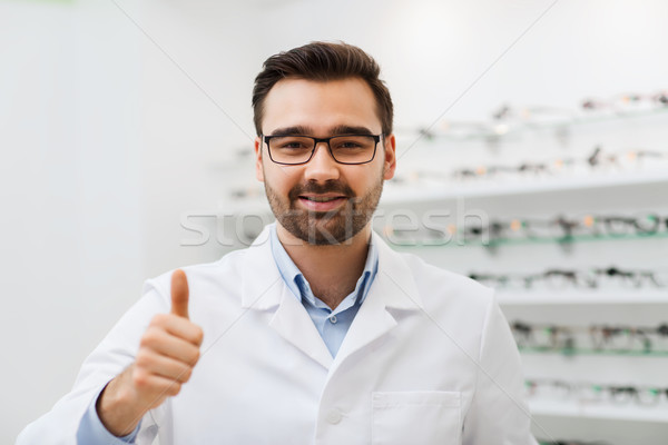 man with glasses and thumbs up at optics store Stock photo © dolgachov