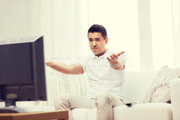 Rozczarowany człowiek oglądania telewizja domu ludzi Zdjęcia stock © dolgachov