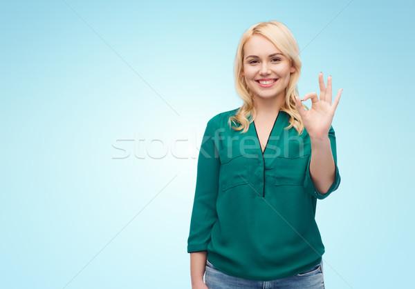 Sorridente mulher jovem camisas sinal da mão Foto stock © dolgachov