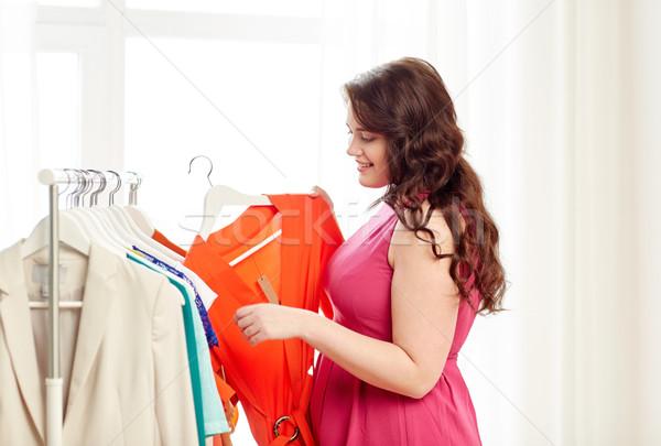 happy plus size woman choosing clothes at wardrobe Stock photo © dolgachov