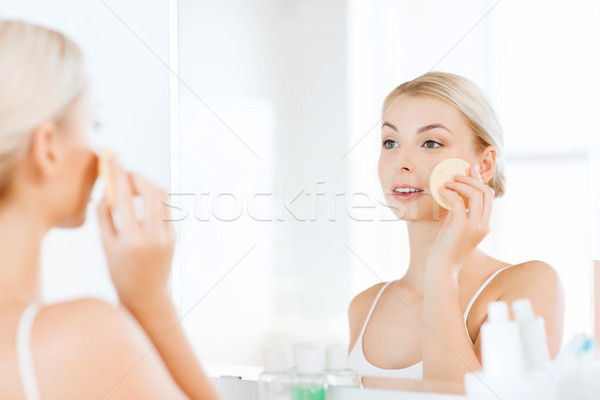 Stock photo: young woman washing face with sponge at bathroom