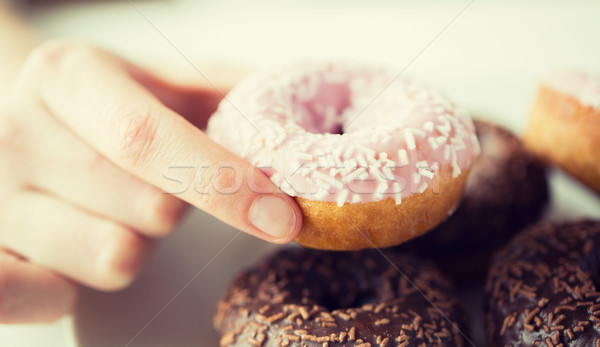 close up of hand holding glazed donut Stock photo © dolgachov