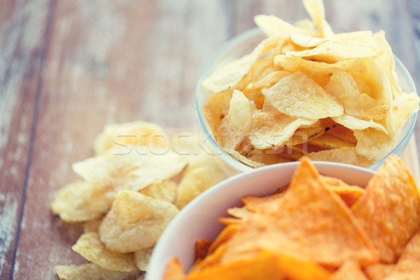 close up of potato crisps and corn nachos on table Stock photo © dolgachov