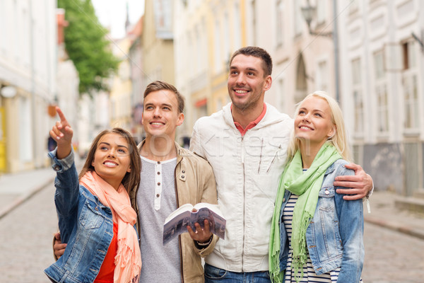 group of friends with city guide exploring town Stock photo © dolgachov