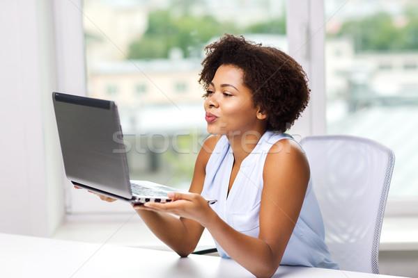 África mujer beso ordenador portátil distante Foto stock © dolgachov