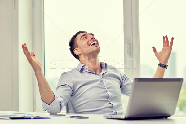 happy businessman with laptop in office Stock photo © dolgachov