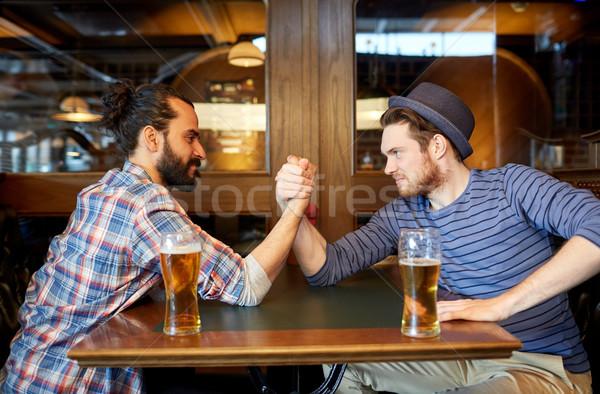 Mannen drinken bier arm worstelen bar pub Stockfoto © dolgachov