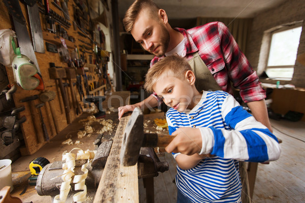 father and son with hammer working at workshop Stock photo © dolgachov
