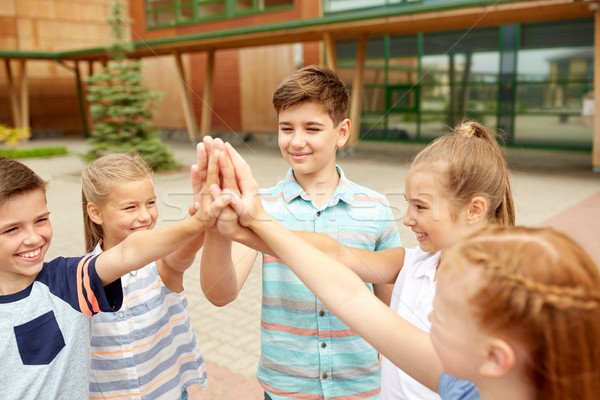 group of children making high five at school yard Stock photo © dolgachov