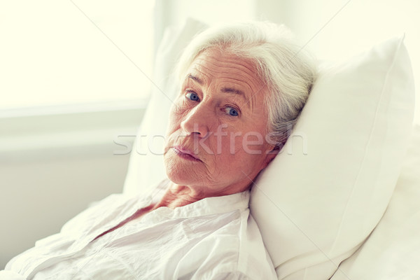 senior woman patient lying in bed at hospital ward Stock photo © dolgachov
