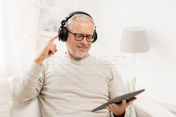senior man with tablet pc and headphones at home Stock photo © dolgachov