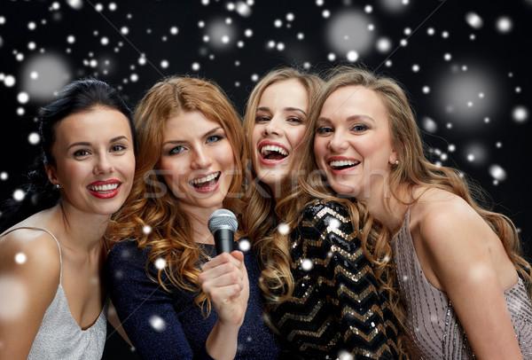 Heureux jeunes femmes micro chanter karaoke nouvelle année Photo stock © dolgachov