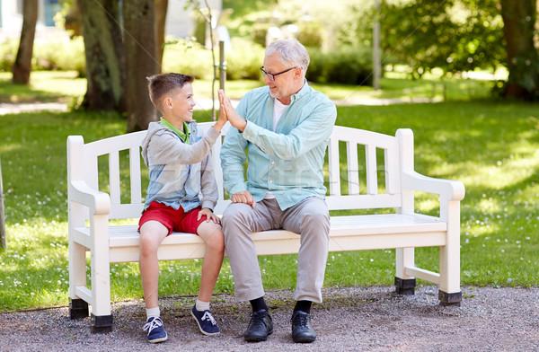 old man and boy making high five at summer park Stock photo © dolgachov