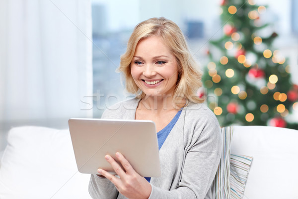 middle aged woman with tablet pc at christmas Stock photo © dolgachov