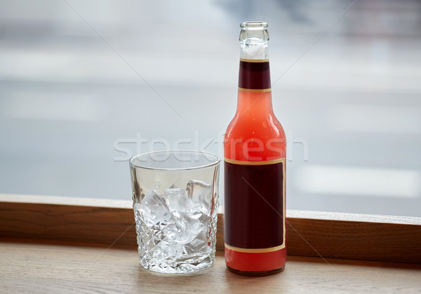 bottle of lemonade and glass with ice on table Stock photo © dolgachov