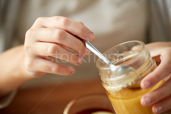 close up of woman hands with honey jar and spoon Stock photo © dolgachov