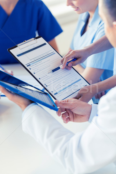 close up of doctors with clipboard at hospital Stock photo © dolgachov