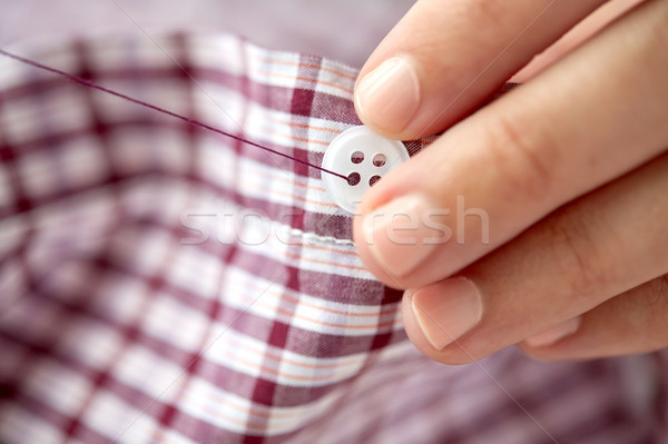 woman with needle stitching on button to shirt Stock photo © dolgachov