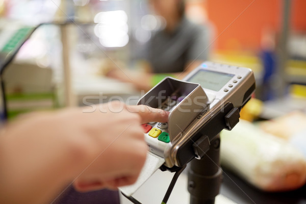 woman entering pin code at store cash register Stock photo © dolgachov