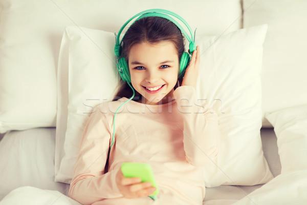 Ragazza felice letto smartphone home persone bambini Foto d'archivio © dolgachov
