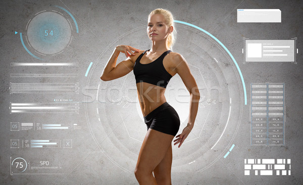 woman in sportswear posing and showing muscles Stock photo © dolgachov
