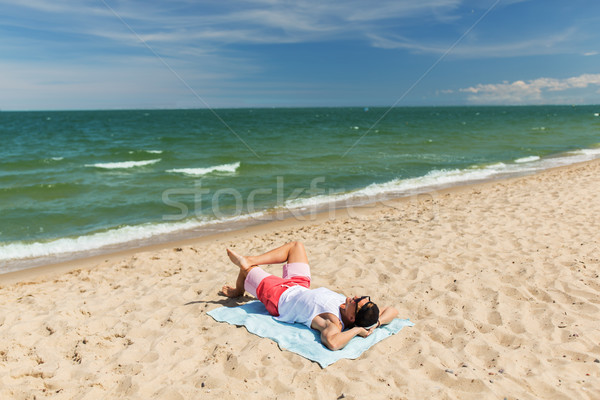 Feliz sonriendo joven tomar el sol toalla de playa verano Foto stock © dolgachov