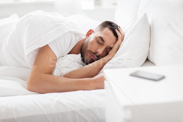 Stockfoto: Man · slapen · bed · smartphone · nachtkastje · mensen