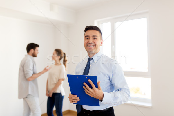 realtor with clipboard and couple at new home Stock photo © dolgachov