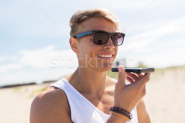 Uśmiechnięty człowiek wzywając smartphone lata plaży Zdjęcia stock © dolgachov