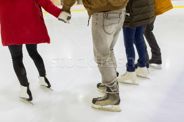 close up of friends on skating rink Stock photo © dolgachov