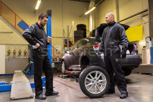 auto mechanics changing car tires at workshop Stock photo © dolgachov