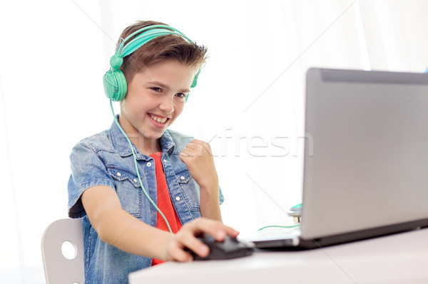 boy in headphones playing video game on laptop Stock photo © dolgachov