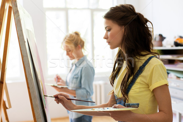 woman with easel painting at art school studio Stock photo © dolgachov