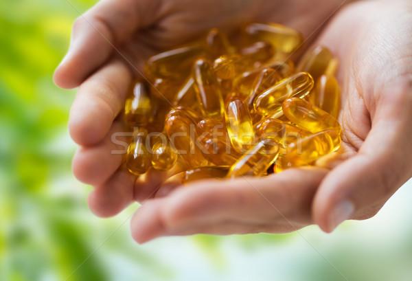 Kezek tart máj olaj kapszulák gyógyszer Stock fotó © dolgachov