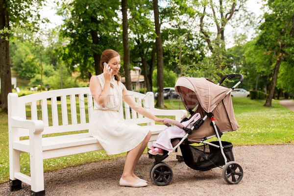 mother with stroller calling on smartphone at park Stock photo © dolgachov