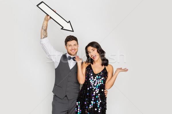 happy couple with big arrow at party Stock photo © dolgachov