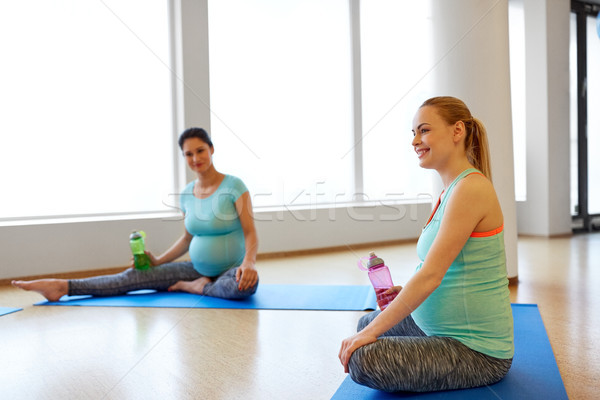 pregnant women with water bottles on mats in gym Stock photo © dolgachov