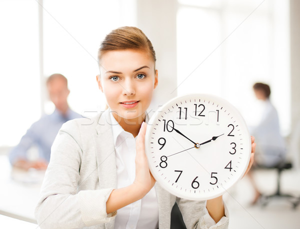 businesswoman showing white clock in office Stock photo © dolgachov