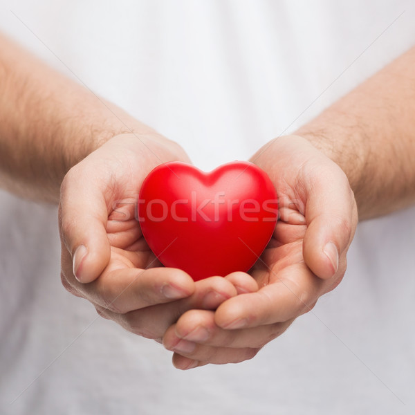 Stock photo: mans cupped hands showing red heart